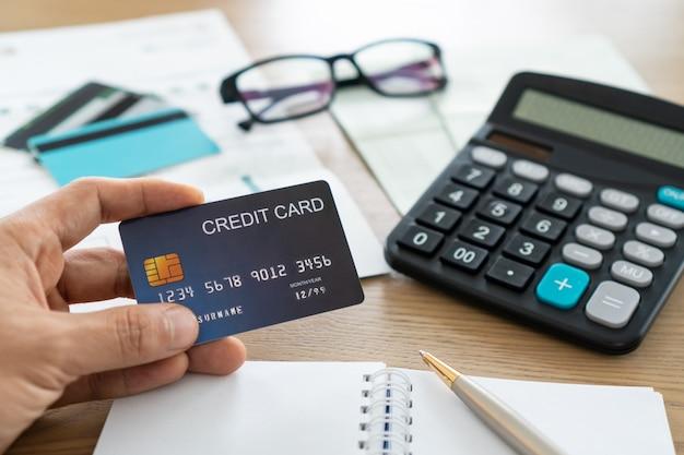 Homem que guarda o cartão de crédito com calculadora, glsasses, cartões de crédito e conta na tabela, conta e conceito de poupança.