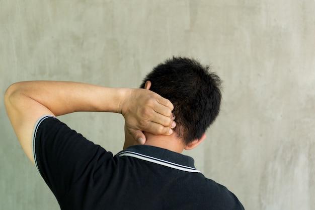 Homem que guarda seu pescoço na dor no fundo cinzento.