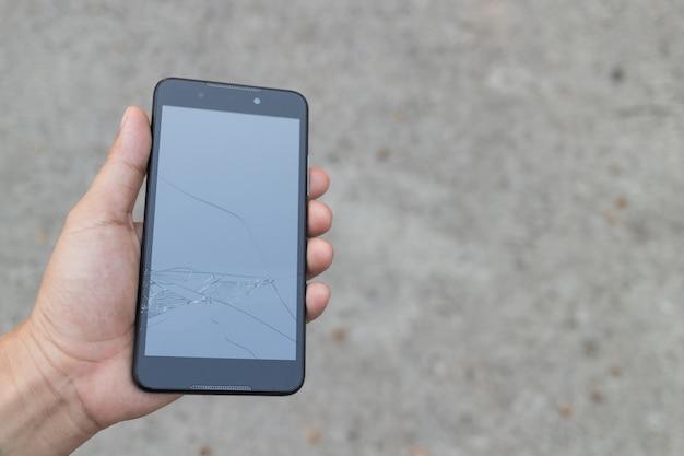 Homem que guarda um smartphone quebrado e dano da tela de toque quebrado.