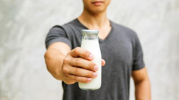 Homem que guarda uma garrafa do leite no fundo cinzento.