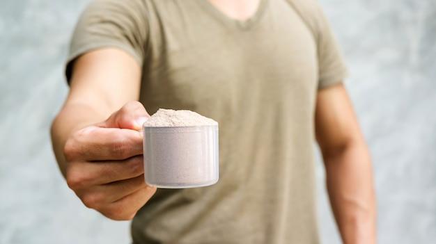 Homem que guarda uma proteína do soro no fundo cinzento.