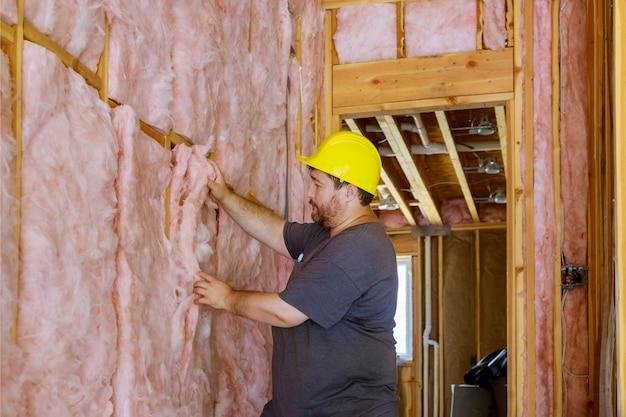 Homem que instala a camada de isolamento térmico sob a parede usando lã mineral