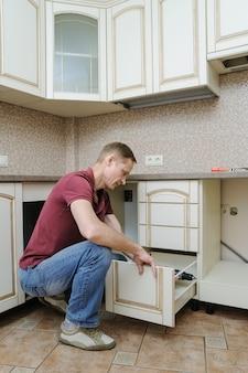 Homem que instala móveis de cozinha