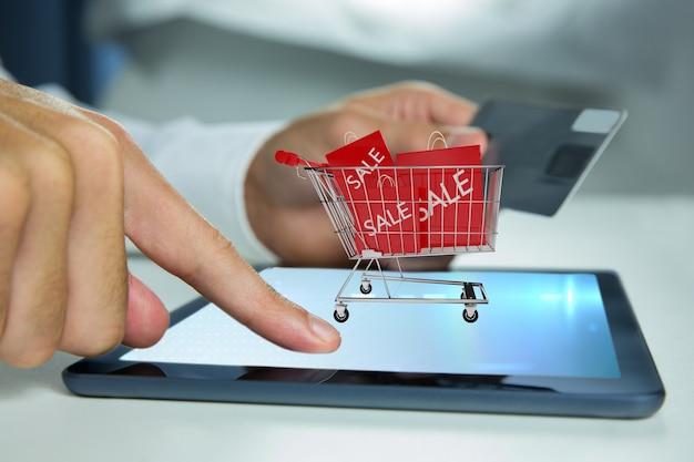 Homem que joga a um tablet com um carrinho de compras