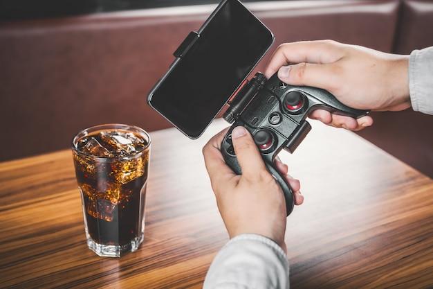 Homem que joga com seu celular e um controlador de vídeo-game