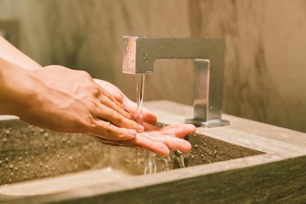 Homem que lava as mãos no local de repouso público. wc moderno estilo de vida sanitário higiênico ou higiênico con