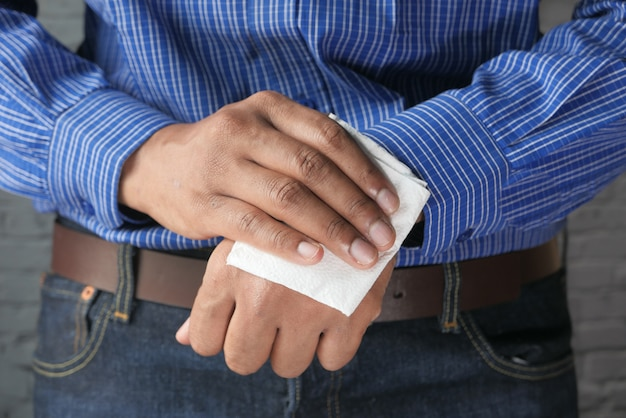 Homem que limpa as mãos com a limpeza molhada anti-séptica.