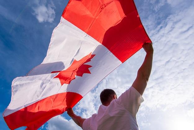 Homem que mantém a bandeira nacional do canadá contra o céu azul