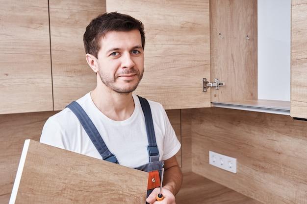 Homem que monta o armário da cozinha. faz-tudo consertando móveis de cozinha