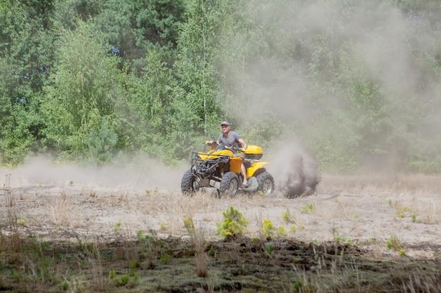 Homem que monta um veículo todo-terreno amarelo de quadriciclo atv em uma floresta arenosa. movimento de esportes radicais, aventura, atração turística.