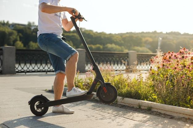Homem que monta uma scooter elétrica ecofriendly em um parque em tempo ensolarado nas calçadas. luz suave