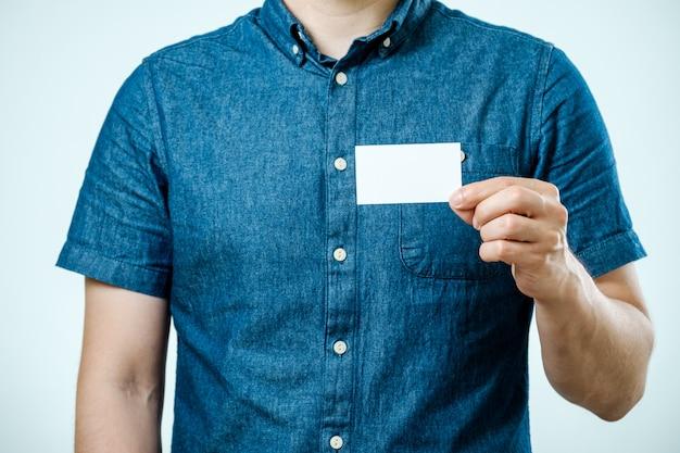 Homem que mostra o cartão em branco branco isolado. concentre-se no cartão