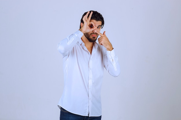 Homem que mostra o sinal da mão do círculo que significa gozo.