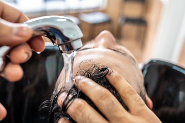 Homem que obtem um cabelo lavado na barbearia.