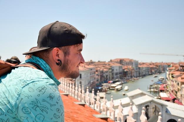 Homem que olha no canal grande em itália, veneza. viagem de homem turista olhando no topo do telhado