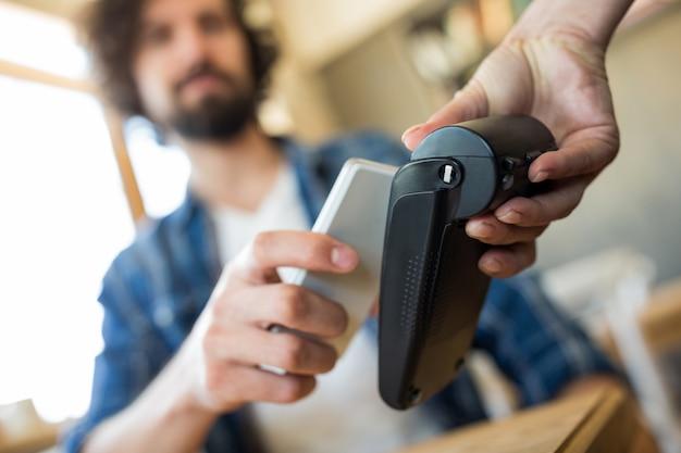 Homem que paga com a tecnologia nfc no telefone móvel