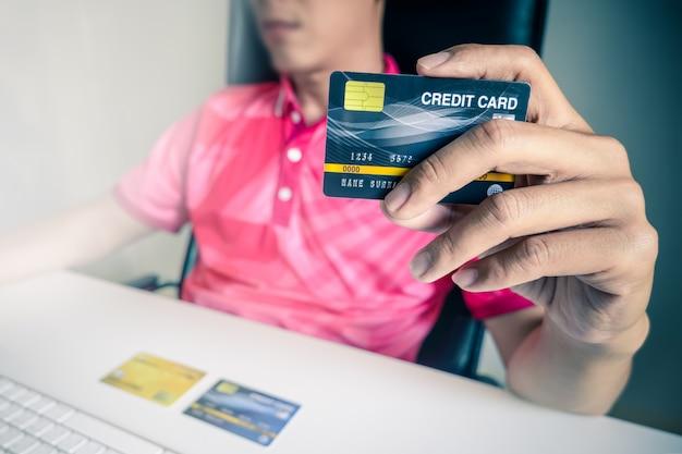 Homem que paga com cartões de crédito no computador em casa.