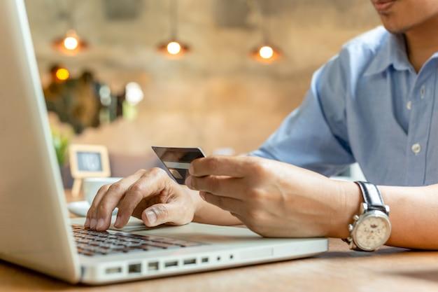 Homem que paga com o cartão de crédito no portátil na cafetaria.