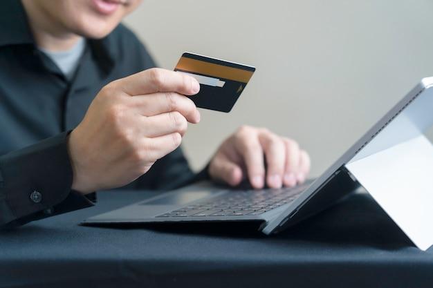 Homem que paga on-line por cartão de crédito com tablet digital ou computador laptop, internet banking ou conceito de comércio eletrônico