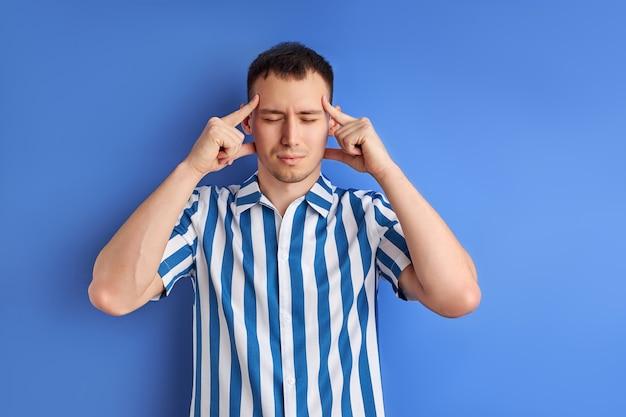 Homem que pensa isolado sobre fundo azul. homem pensativo concentrado em pensamentos, de pé com os olhos fechados e segurando as têmporas