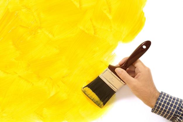 Homem que pinta uma parede amarela Foto gratuita