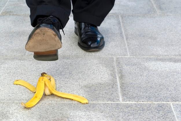 Homem que pisa na casca da banana
