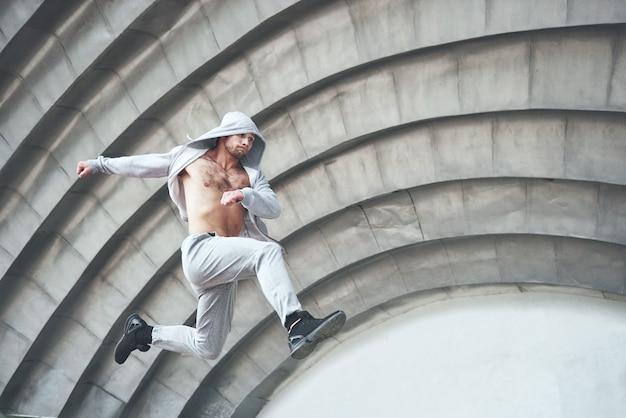 Homem que pratica parkour pulando no treino de rua.