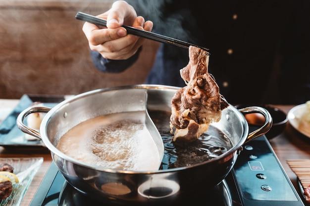 Homem que prende a fatia rara média wagyu a5 para fora do shabu quente do potenciômetro por chopsticks com vapor.