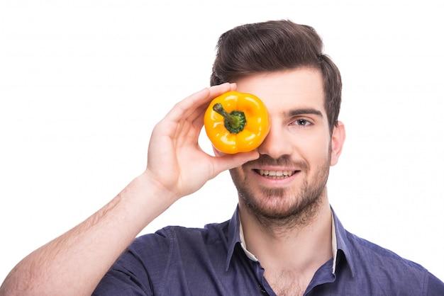 Homem que prende a pimenta amarela perto de seus olhos.