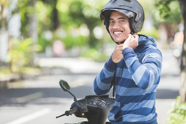 Homem que prende seu capacete de moto
