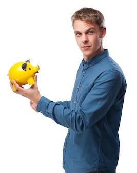 Homem que prende um banco piggy porco amarelo