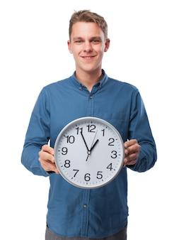 Homem que prende um grande relógio