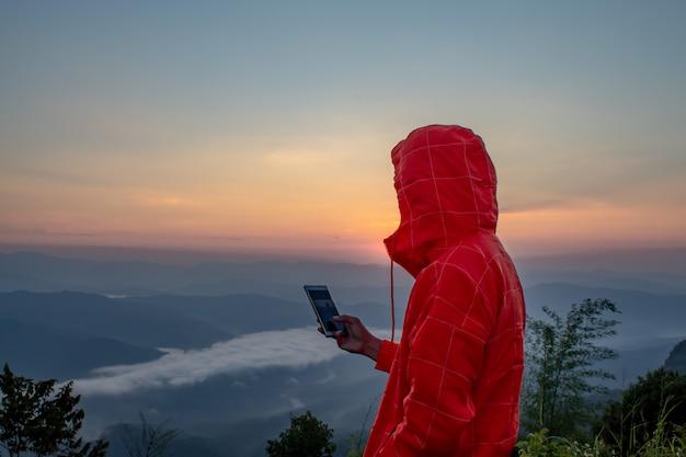 Homem que prende um telefone móvel na montanha com o sol e a névoa.
