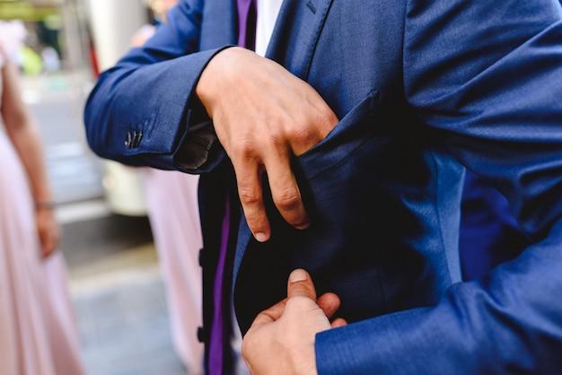 Homem que prepara e que veste-se em um terno sóbrio e elegante para um evento.