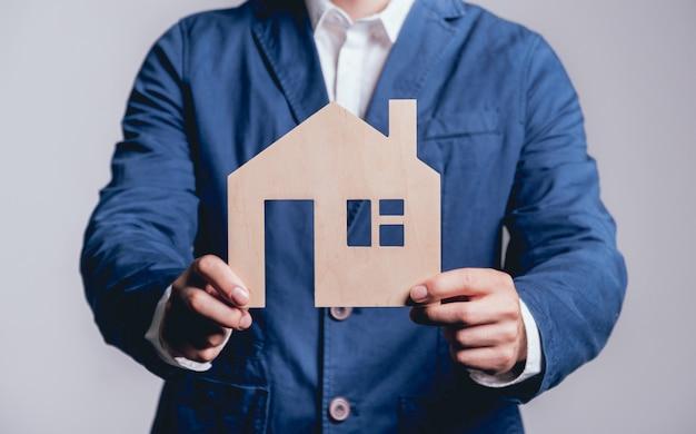 Homem que propõe assinar uma apólice de seguro imobiliário, o agente está segurando o modelo da casa de madeira. conceito de seguro imobiliário.