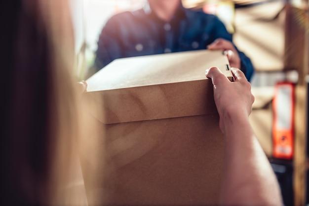 Homem que recebe o pacote do correio