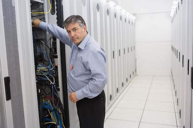 Homem que repara fios de servidores