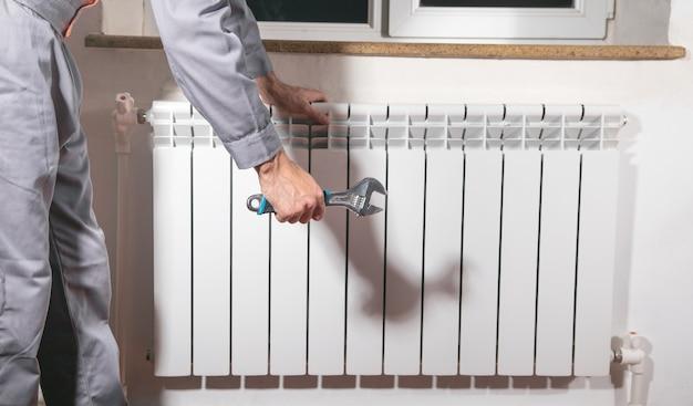 Homem que repara o radiador com chave ajustável.
