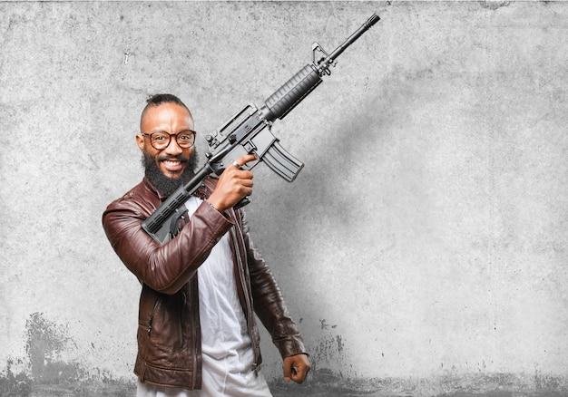 Homem que ri enquanto aponta uma metralhadora para o céu