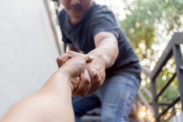 Homem que salvar outro agarrando o antebraço que salva e que ajuda o conceito.