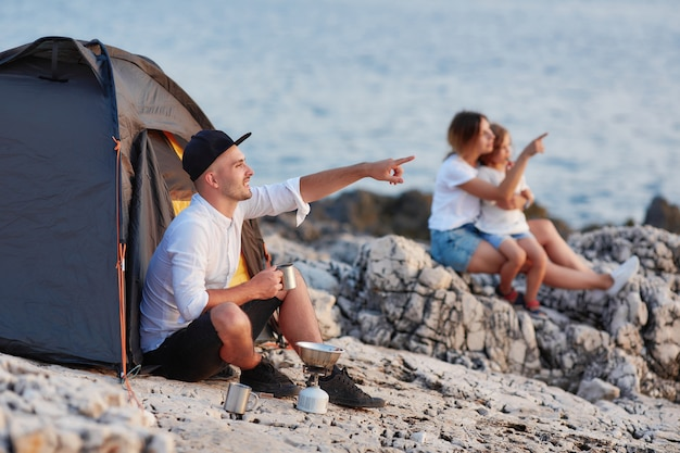 Homem que senta-se na praia rochosa que olha o por do sol, a esposa e a filha sentando-se próximo.