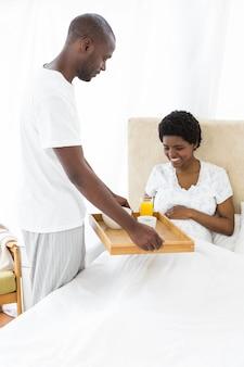 Homem que serve café da manhã a mulher grávida na cama em casa