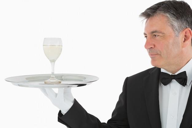 Homem que serve um copo de vinho na bandeja