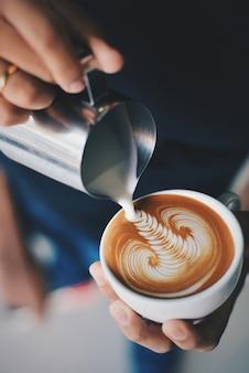 Homem que serve uma xícara de café