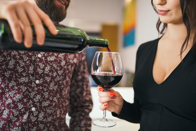Homem que serve vinho para mulher tendo data