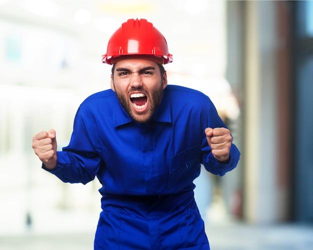 Homem que shouting com um macacão azul de trabalho