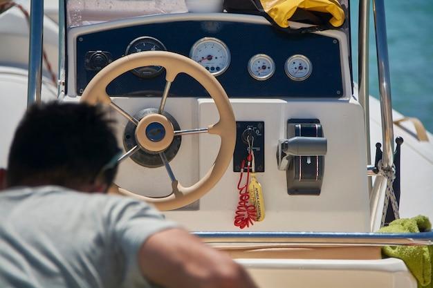 Homem que sobe no barco de borracha com o console de guias à sua frente.