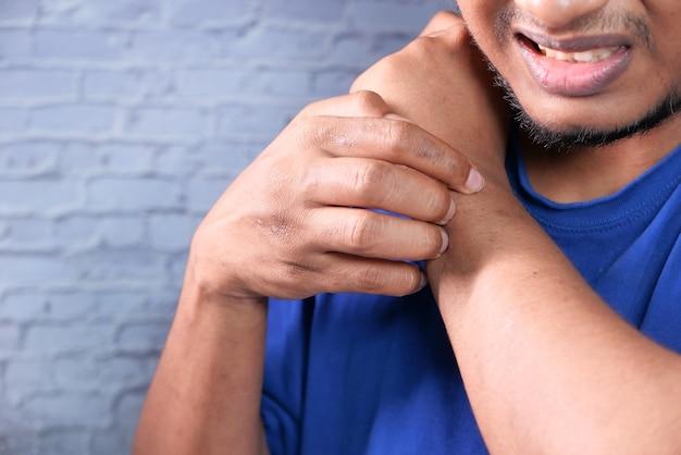 Homem que sofre de coceira na pele, close-up.