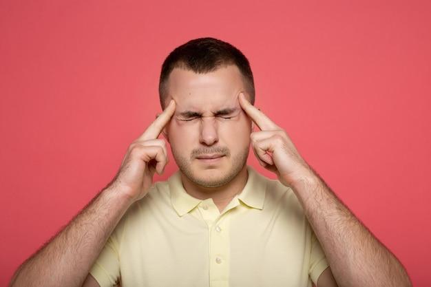 Homem que sofre de dor de cabeça no rosa