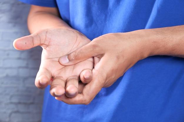 Homem que sofre de dor na mão close-up.